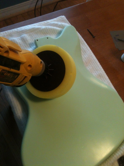 Buffing the newly painted electric guitar