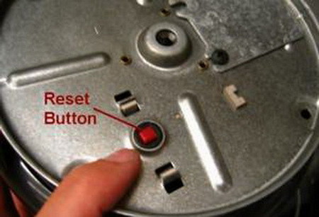 red reset button on the bottom of a garbage disposal